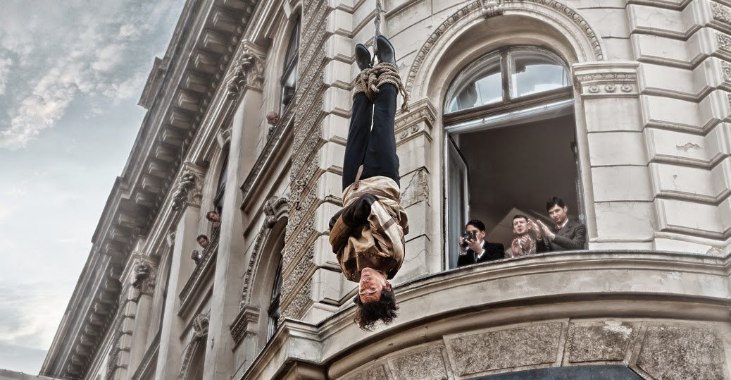 Adrien Brody as Harry Houdini in straitjacket performing a daredevil trick in History Channel TV Mini-Series