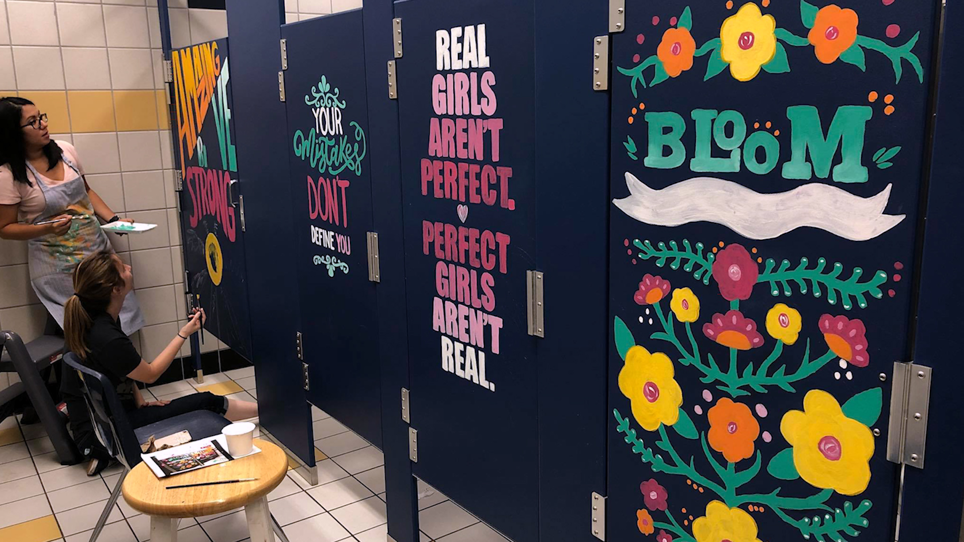 middle school teachers paint encouraging words on girls bathroom stalls
